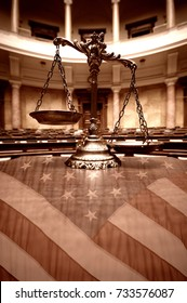 Symbol of law and justice in the empty courtroom, law and justice concept. Scales of justice and United States flag.