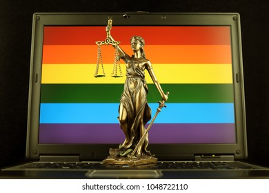 Symbol of law and justice with Rainbow Flag on laptop. Studio shot.