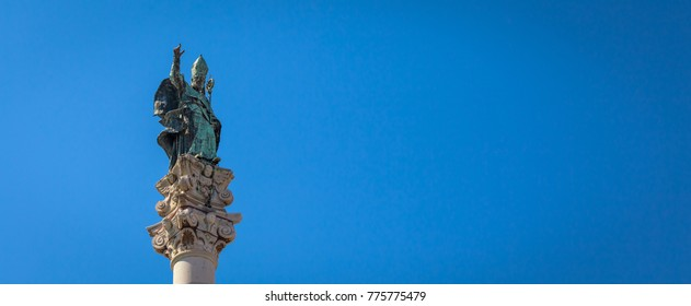 The symbol of Lecce town (Italy): Saint Oronzo (Sant'Oronzo) posed on the column at the center of the main town Square. Blue backgroud with copy space.