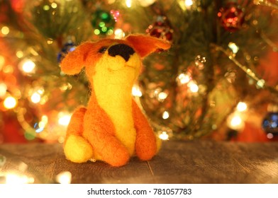 Symbol of new years 2018 cur dog. New years greetings background. Fancy handmade toy from wool on bokeh Christmas background. Place for insert logo or write text. Copyspace for congratulations.