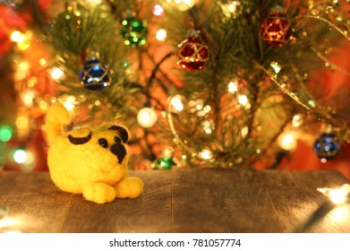 Symbol of new years 2018 round yellow dog. New years greetings background. Fancy handmade toy from wool on bokeh Christmas background. Place for insert logo or text. Copyspace for congratulations.