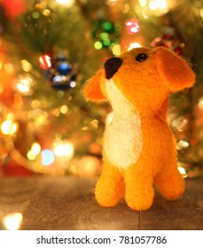 Symbol of new years 2018 yellow dog. New years greetings background. Fancy handmade toy from wool on bokeh Christmas background. Place for insert logo or write text. Copyspace for congratulations.
