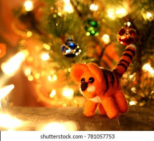 Symbol of new years 2022 tiger. New years greetings background. Fancy handmade toy from wool on bokeh Christmas background. Place for insert logo or write text. Copyspace for congratulations.
