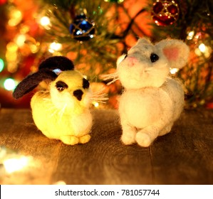 Symbol of new years 2023  Love Rabbit. New years greetings background. Fancy handmade toy from wool on bokeh Christmas background. Place for insert logo or write text. Copyspace for congratulations.