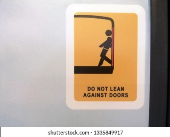 The symbol on the train says Do not lean  against doors.