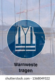 Symbol on a transparent tarpaulin as an indication of safety on a construction site. You can see that you should wear a safety vest. The text means in German: Wear a safety vest.