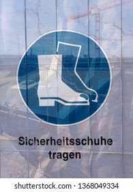 Symbol on a transparent tarpaulin as an indication of safety on a construction site. You can see that you should wear safety shoes. The text means in German: Wear safety shoes.