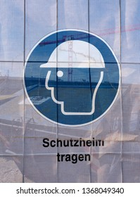 Symbol on a transparent tarpaulin as an indication of safety on a construction site. You can see that you should wear a hard hat. The text means in German: Wear a hard hat.