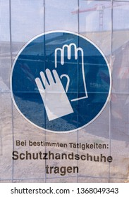 Symbol on a transparent tarpaulin as an indication of safety on a construction site. You can see that you should wear work gloves. The text means in German: Wear work gloves.