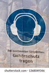 Symbol on a transparent tarpaulin as an indication of safety on a construction site. You can see that you should wear earmuffs. The text means in German: Wear earmuffs.