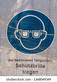 Symbol on a transparent tarpaulin as an indication of safety on a construction site. You can see that you should wear safety goggles. The text means in German: Wear safety goggles.