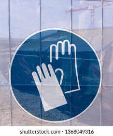 Symbol on a transparent tarpaulin, through which parts of the jobsite are seen, as an indication of safety on a construction site. You can see that you should wear work gloves.