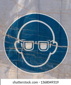 Symbol on a transparent tarpaulin, through which parts of the jobsite are seen, as an indication of safety on a construction site. You can see that you should wear safety goggles.