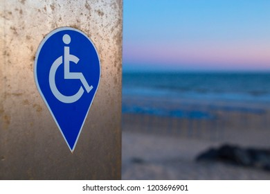 Symbol for people with disability adapted devices. Sunset backgroun at beach
