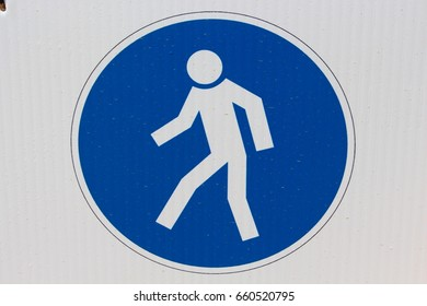 Symbol of person walking in blue circle