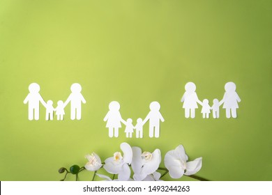 Symbol of same-sex families, protection of sexual minorities, a family of white paper. Green background and orchid flowers. View from the top there is a place for inscription.