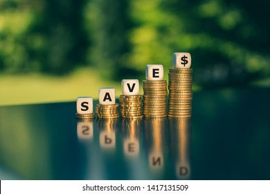 """Symbol for saving or spending money. Dice form the word """"save"""" while the word """"spend"""" is visible in the reflection."""