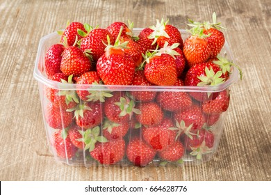 Symbol of summer, a punnet of delicious fresh strawberries on wooden table