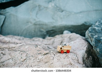 Symbol of travel, adventure and dreams. Miniature wooden truck full of rocks