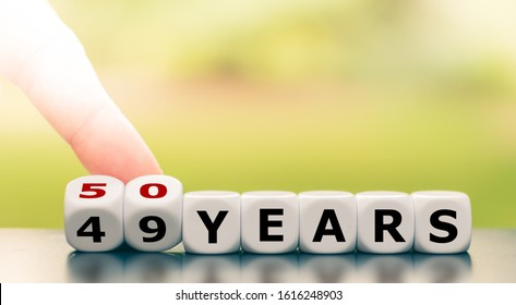 """Symbol for turning 50 years old. Hand turns a dice and changes the expression """"49 years"""" to """"50 years""""."""