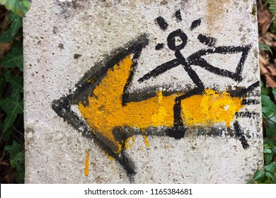 Symbol of the Way of Saint James, or Camino de Santiago, with a yellow shell and a yellow arrow with a man on it