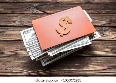symbol of a wooden dollar on a book on the background of a wooden table. finances, money savings. deposits in the bank.