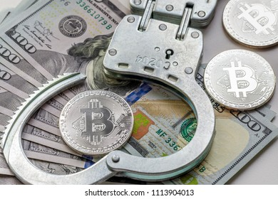 Symbolic coins of bitcoin and handcuffs on banknotes of one hundred dollars. Exchange bitcoin for a cash dollar, but be a law-abiding citizen.
