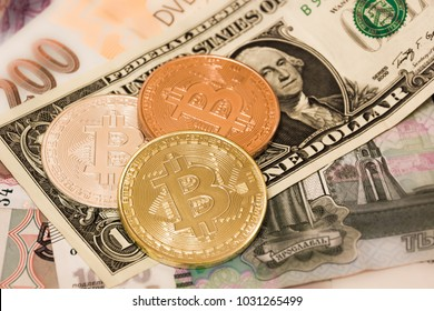 Symbolic coins of bitcoin on banknotes of US dollars, czech crowns and Russian rubles.