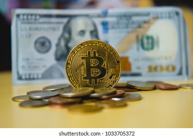 A symbolic coins of bitcoin on banknotes of one hundred dollars exchange bitcoin cash for a dollar