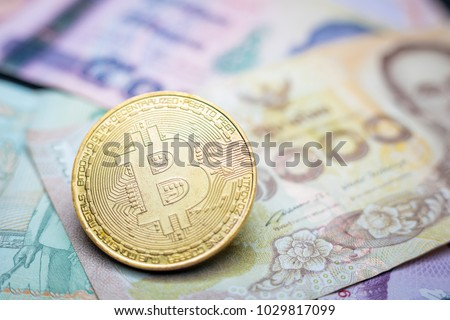 Symbolic coins of bitcoin on banknotes of one hundred dollars. Exchange bitcoin cash for a Thai baht
