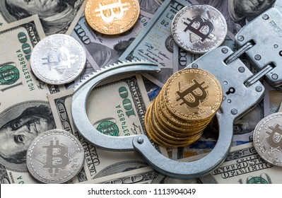 Symbolic coins of bitcoin and stack of   bitcoin coins and metall handcuffs on banknotes of one hundred dollars. Exchange bitcoin for a cash dollar, but be a law-abiding citizen.