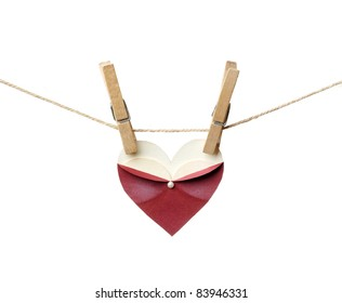 Symbolic female heart shape hanging on the clothesline. Isolated on white. Wedding or st.Valentine theme.
