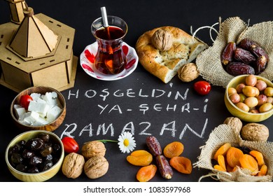 Symbolic foods of Ramadan around handwriting text,Welcome Ramadan by Turkish letters on the black background.Wooden model mosque near foods.Fasting foods before main menu.