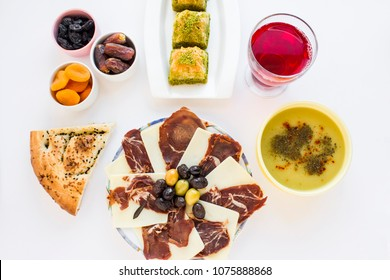 Symbolic foods of Ramadan,dried age,meat,black olives,lentil soup,pide (Ramadan bread),traditional Turkish dessert baklava and cold,savory,sweet sherbet on the white surface.Close up taken,isolated.