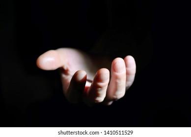 Symbolic hand helping on black background