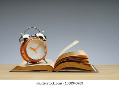symbolic hard study is powerful to succeed, concept with book and alarm clock