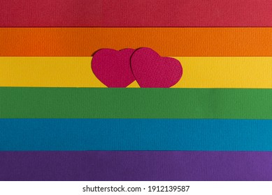 symbolic hearts cut out of paper on the background of the LGBT flag made of paper.