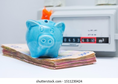 The symbolic image of the high cost of natural gas for heating homes in the cold season. Blue piggy bank with pile of money near the gas meter. Selective focus, close-up. - Shutterstock ID 1511230424