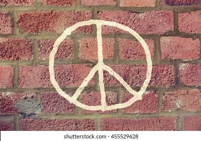 symbolic, pacifism and hippie concept - peace sign drawing on red brick wall