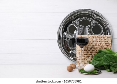 Symbolic Pesach (Passover Seder) items on white table, space for text