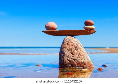 Symbolic scales made of stones on the sea background. Concept of harmony and balance. Pros and cons, work - life concept