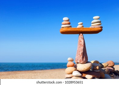 Symbolic scales of stones on a background of blue sky and sea. Concept of harmony and balance. Pros and cons concept. Work life balance