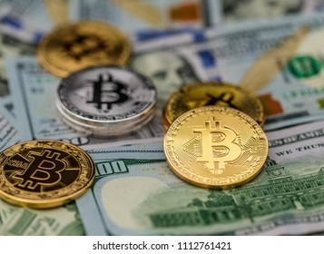 Symbolic silver and gold coins of bitcoin on banknotes of one hundred dollars and one dollar. Exchange bitcoin cash for a dollar.