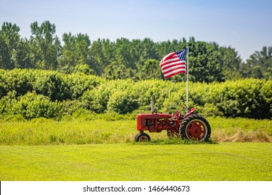 Symbols of American farming: tractor and flag on summer day