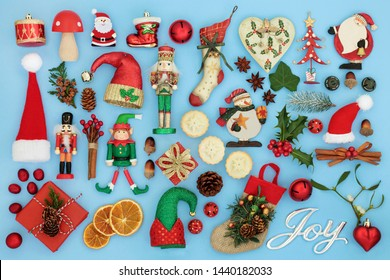 Symbols of Christmas with silver joy sign, retro bauble tree decorations, flora and food selection on pastel blue background Traditional symbols for the festive season.