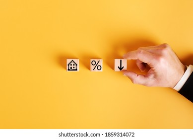 symbols house, percent and down arrow on wooden cubes and orange background. concept of low cost real estate