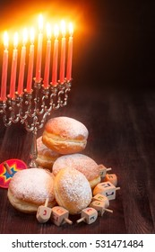 Symbols of jewish holiday hanukkah - menorah, donuts sufganiyot and dreidels. Copyspace background.