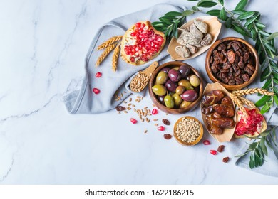Symbols of judaic holiday Tu Bishvat, Rosh Hashana new year of the trees. Mix of dried fruits, date, fig, grape, barley, wheat, olive, pomegranate on a marble table. Copy space background