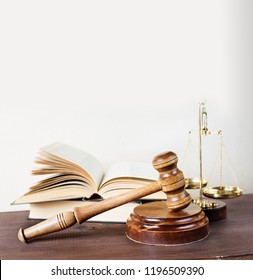 Symbols of law: wood gavel, soundblock, scales and opened volumetric old books; square image with copy-space