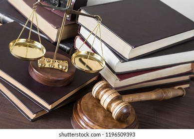Symbols of law: wood gavel, soundblock, scales and pile of volumetric old books